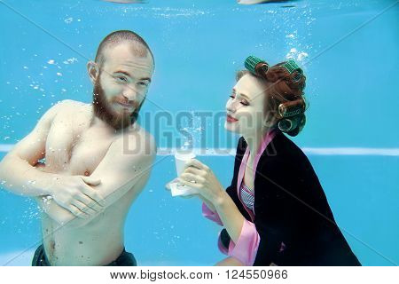 couple - girl in a bathrobe and curlers, and a bearded man drinking coffee underwater in the swimming pool