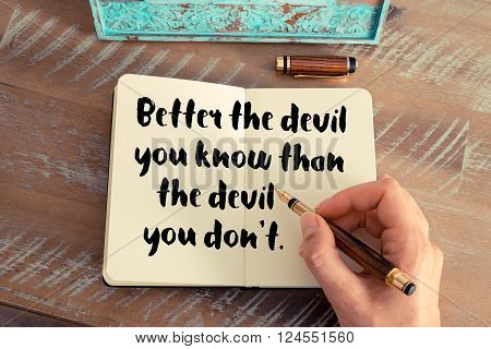Retro effect and toned image of a woman hand writing on a notebook. Handwritten quote Better the devil you know than the devil you don't as inspirational concept image