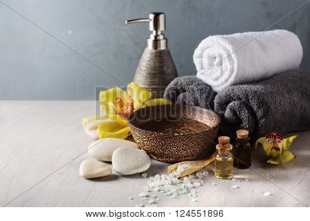 Beautiful spa composition with orchid flower and massage oil on table. SPA background with copyspace