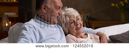Older couple in love spending nice evening together sitting on a couch
