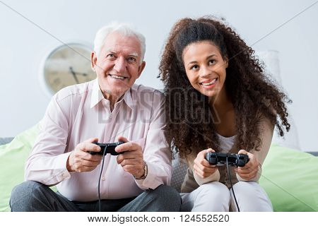 Senior happy man playing in video games with young pretty caregiver