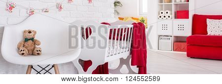 Perfect cozy space with chair and cradle for mother and her baby in spacious modern bedroom