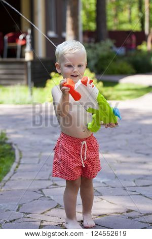 Portrait of blonde baby boy playing with water toy in the summer park