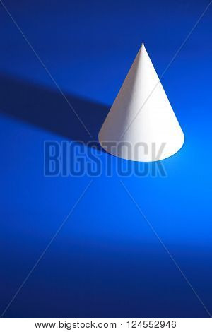 Geometry concept. One white paper cone on blue background