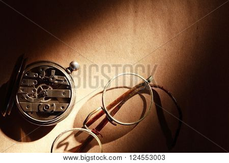 Old spectacles near closed pocket watch on brown paper background