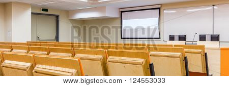 Photo of row of wooden comfortable chairs on medical university. Classroom prepared for lectures
