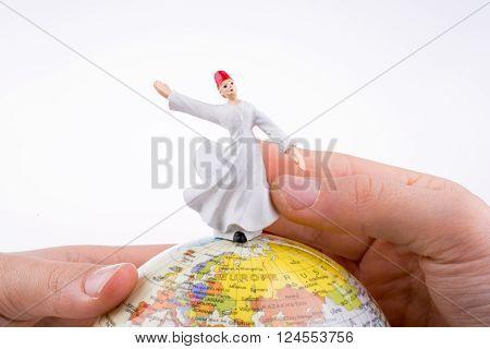 Hand holding a Sufi Dervi? on a globe