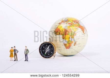 A couple by the side of a globe with a compass on isolated white background