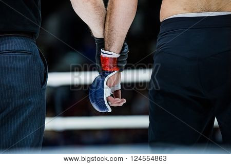 judge holds hand of boxer before announcing winners in a fight