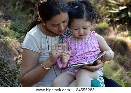 Mother reading book with her 2 year old child.
