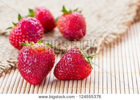 Fresh strawberries on sack with wooden background