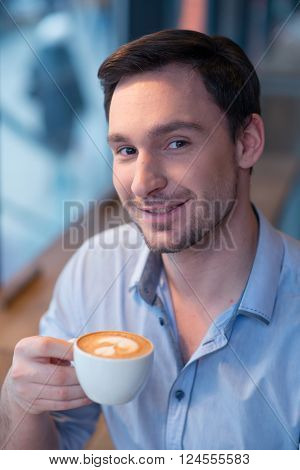 Revel in best taste. Portrait of handsome delighted man holding cup of coffee and drinking it while smiling