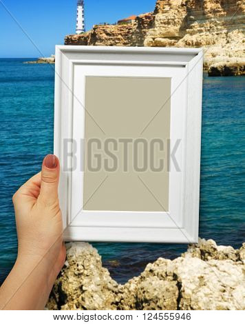 Wooden frame in beautiful woman hands on the sea background