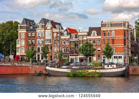 Boat on city canal and typical houses on background in Amsterdam, Netherlands.