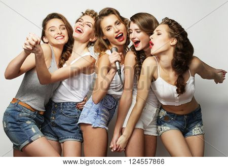 group of  beautiful stylish hipster  girls singing karaoke