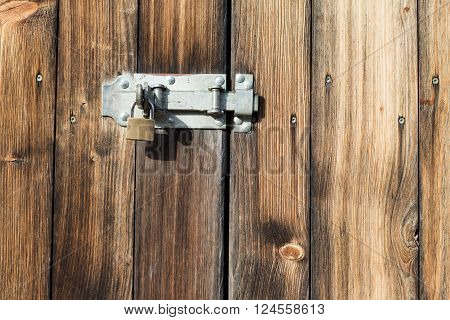 old wooden door with padlock and metal latch