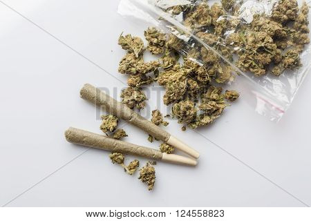 Pile of medical cannabis dried buds scattered from nylon package and two marijuana joints on white background directly from above