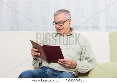 Senior man enjoys reading book at home.
