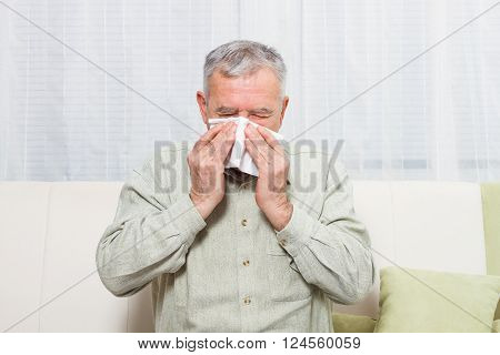 Senior man is sitting on sofa and sneezing into handkerchief.