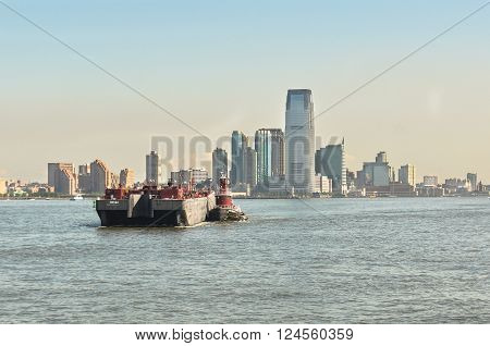 Manhattan,New York,USA - June 27, 2011 : Barge towed by a tugboat on Hudson River