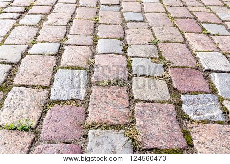 Cobbled pavement made of red and gray cobblestone.Closeup.Small depth of field.