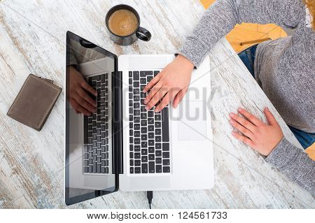 A working womans hand at a table with laptop tablet and phone.