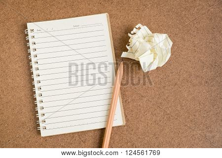 Open spiral notebook with crumpled paper ball and pencil on brown texture background