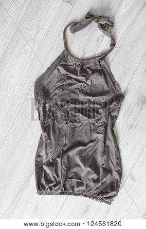Crumpled gray halter top on wooden floor as a background