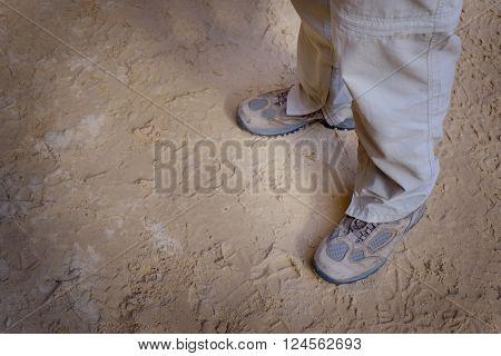 Hiker wearing hiking boots muddy sitting on rock
