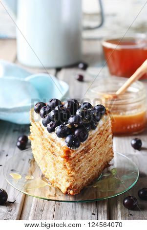 Piece of honey cake decorated with blueberry and honey on glass dish