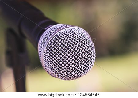Black and silver microphone with green outdoor background.