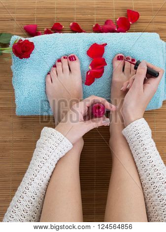 Top View Of Woman Applying Nail Varnish To Toe Nails