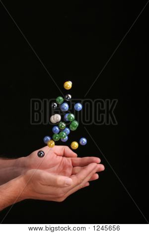 Catching Falling Marbles Against A Black Background