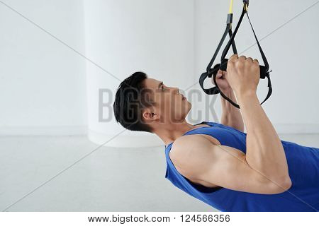Asian young man performing trx chest exercise in the gym