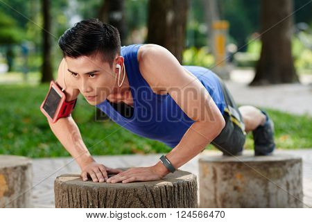 Sweaty determined young Vietnamese sportsman doing push-ups