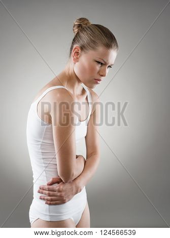 Abdomen or menstruation pain. Young woman touching her abdomen in pain.
