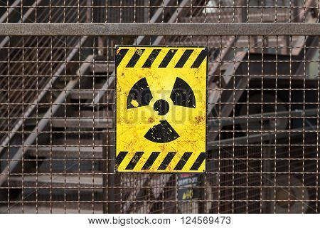 yellow radioactive warning sign on rusty fence