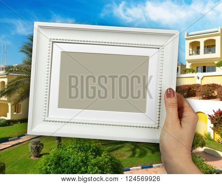 Wooden frame in beautiful woman hands. background of the Egyptian hotel