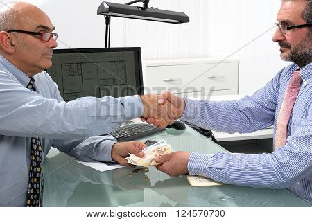 Handshake between businessmen engaged in a financial transaction with banknotes of the Euro