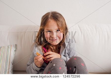 Little girl at home sitting on sofa eating breadsticks. Happy child playing indoors.