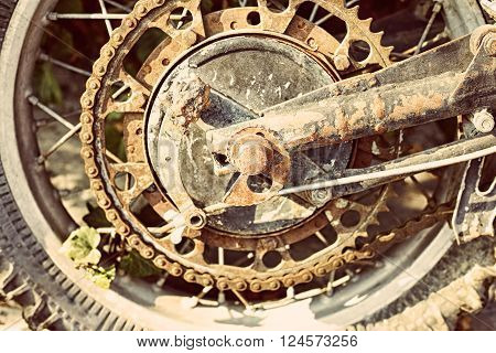 Old dirty motorcycle chain on wheel with rusty metal parts.