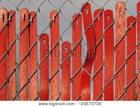 Vertical slats in a red fence are slipping earthward.