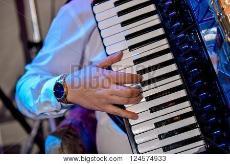 The person who plays the accordion on stage
