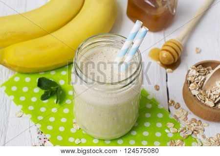 Banana smoothies in a glass jar on a white background