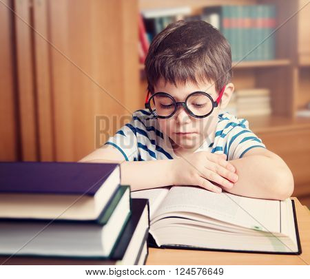 seven years old child reading a book at home