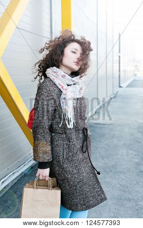 Happy girl finishes shopping. In the hands packages with purchases. Make purchases with pleasure. Girl in a coat in the spring, wavy curly hair is developing the wind, full portrait outdoors growth.