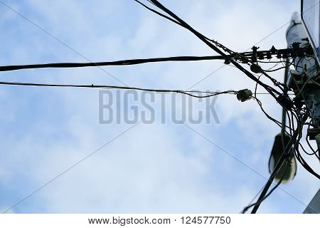 electrical wires on a lamppost on the sky background