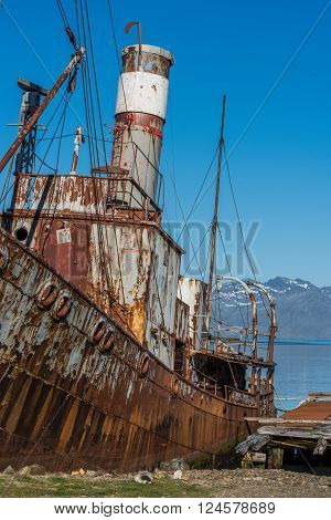 Close-up of rusty whaler moored by jetty