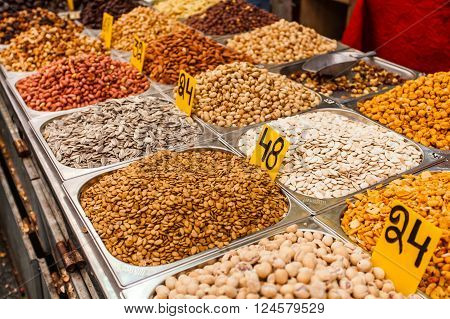 Close-up of different nuts and seeds in metal boxes. The counter on the Mahane Yehuda Market in Jerusalem, Israel.