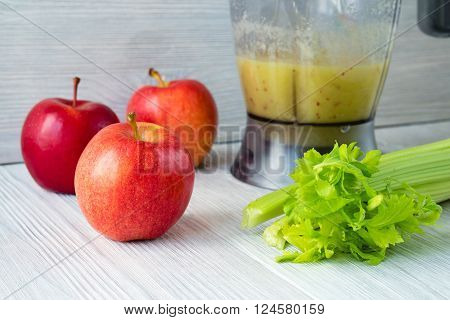 Apples And A Bunch Of Celery, And A Food Processor With A Smoothie On A White Table